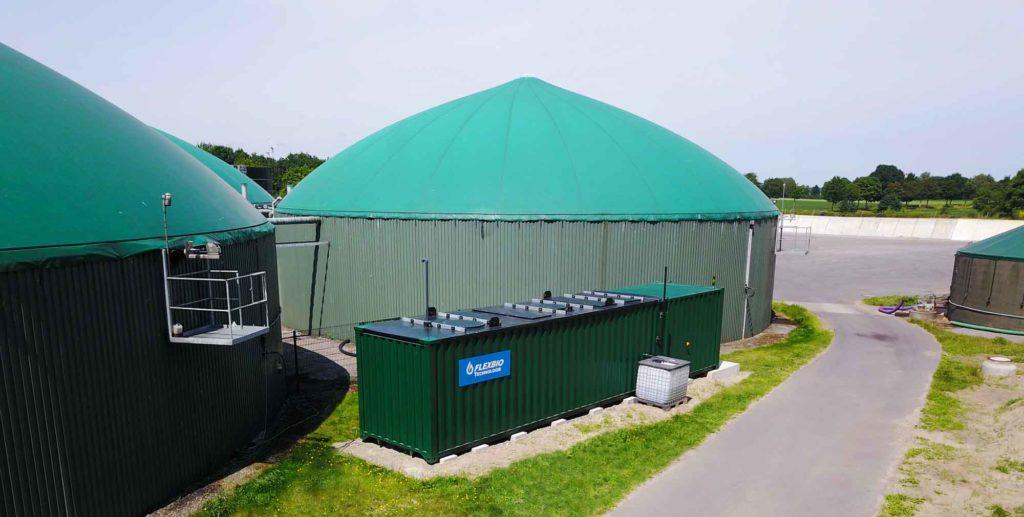 eine grüne Containeranlage von der FlexBio Technologie GmbH vor einer Biogasanlage