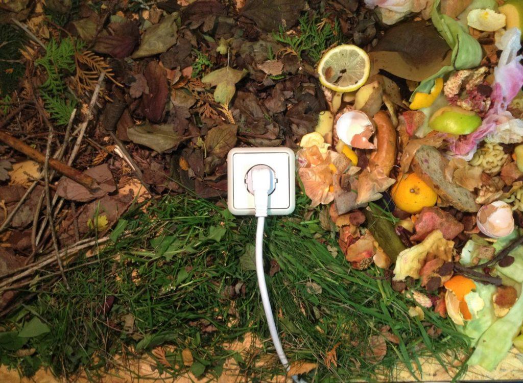 eine Steckdose mit einem Stecker, der auf einem Waldboden liegt neben Abfall