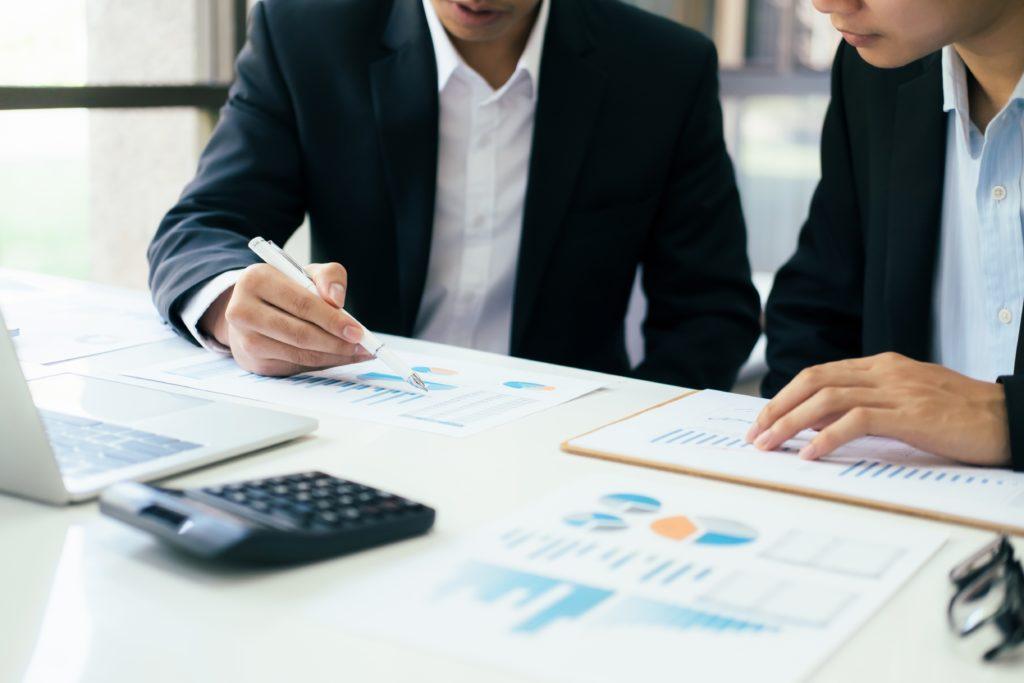 zwei Männer im Anzug, die in einem Geschäftsmeeting zur Besprechung des Investments sind mit Statistiken, einem Taschenrechner und einem Laptop