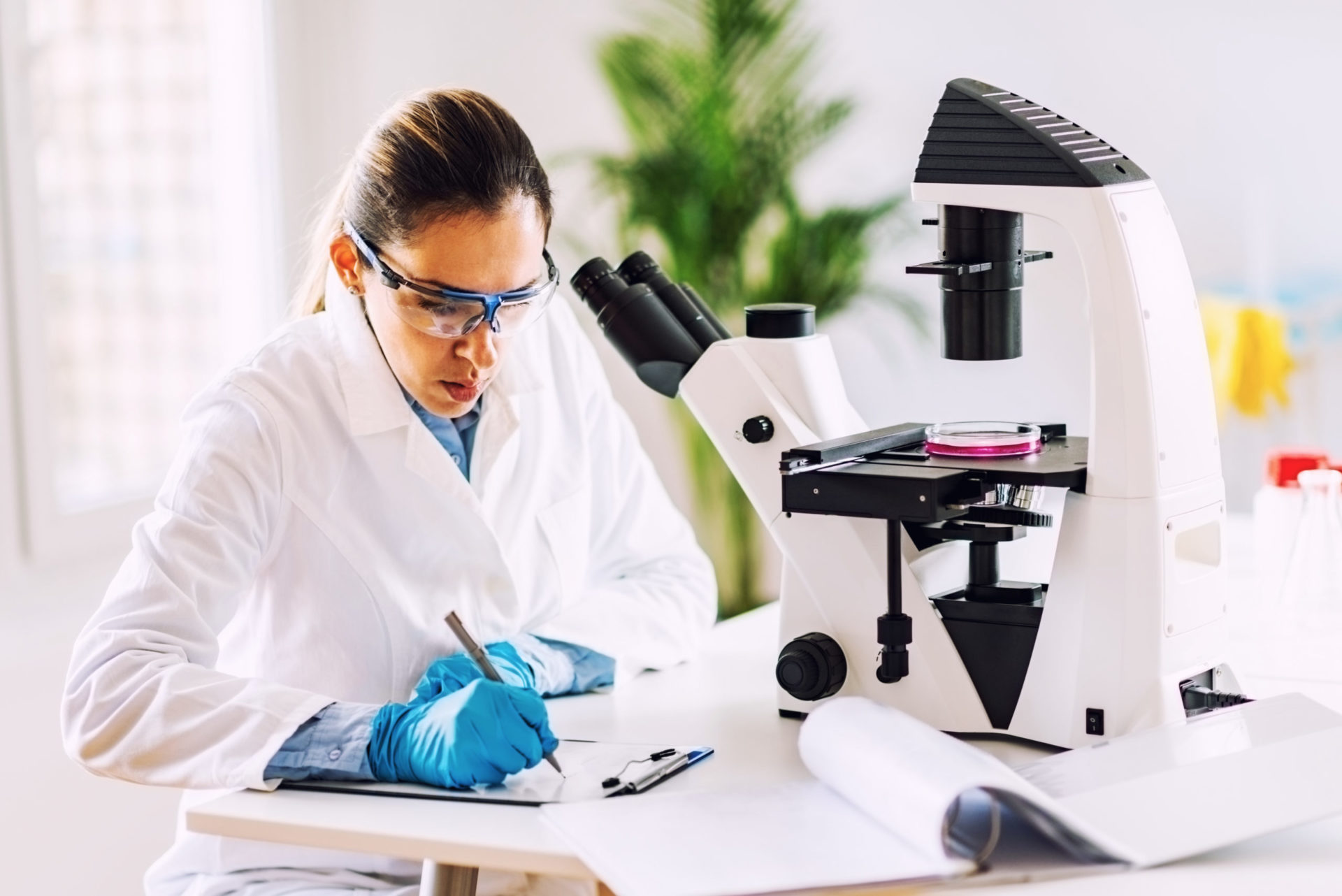 a microbiologist with safety glasses, a white coat and blue gloves who has examined bacteria with the help of a large microscope and takes notes
