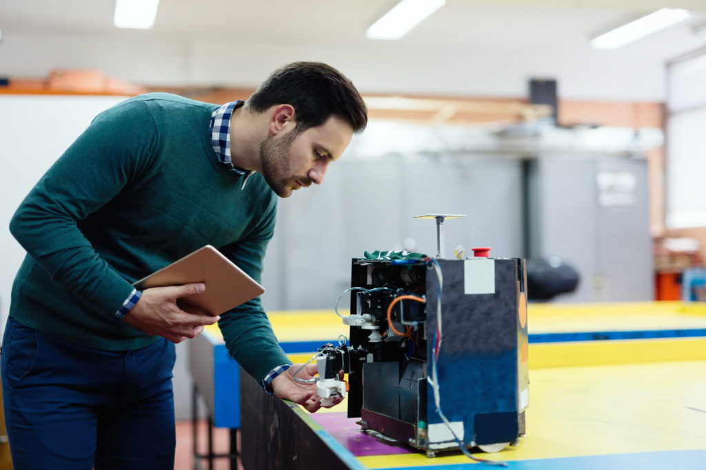 a young engineer testing his robot in a workshop