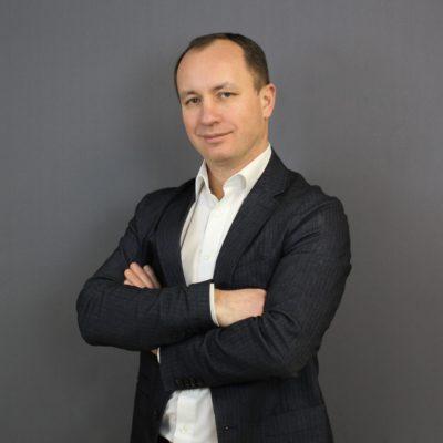 Ein Portrait von dem Chief Technology Officer Waldemar Ganagin vor einem grauen Hintergrund