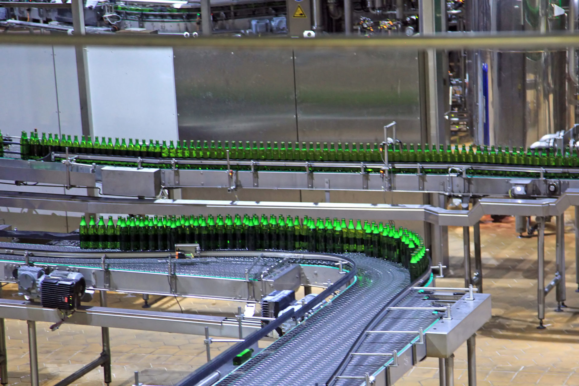a conveyor belt with green beer bottles that are filled with beer in a brewery