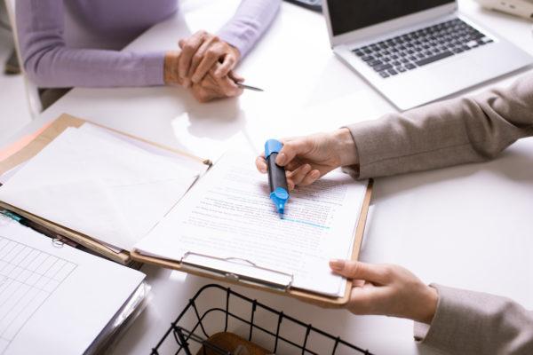 Nahaufnahme von einem Berater, der ein Formular mit einer markierten Stelle einem Kunden zeigt und erklärt