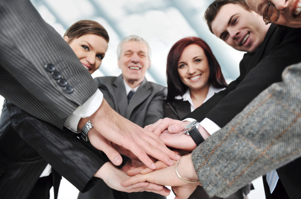 Entrepreneurs standing in a circle with hands on top of each other smiling at the camera