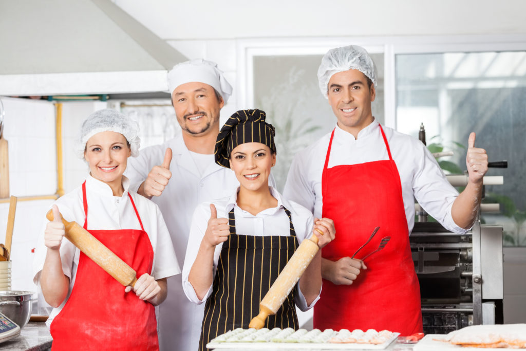 a chef with his staff in work clothes smiling and showing a thumbs up at the camera