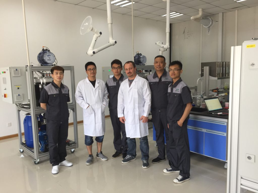 five Chinese men and the Chief Technology from FlexBio Technologie GmbH in work clothes standing in front of the test facilities of FelxBio Technologie GmbH in a laboratory in China