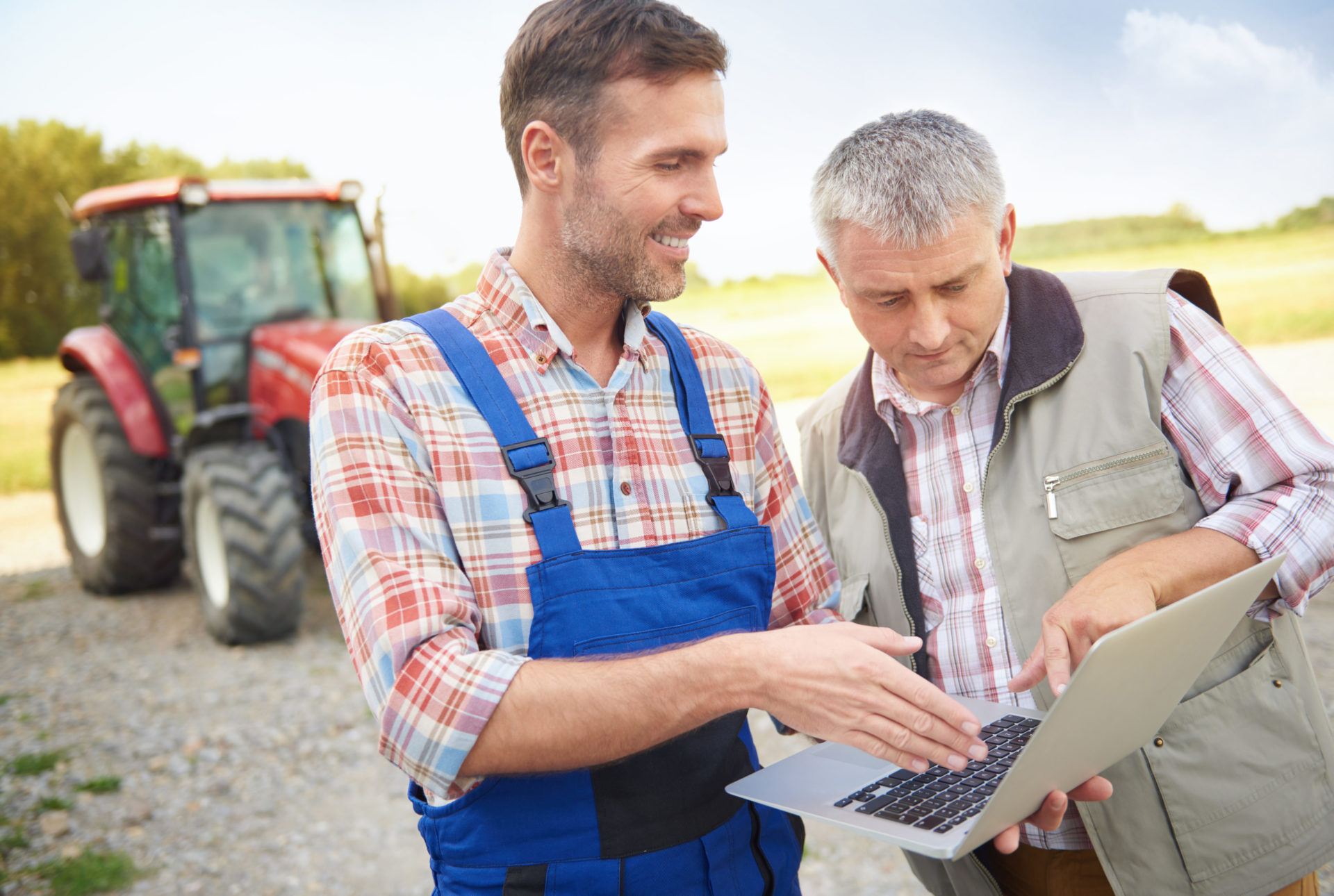 two men from the agricultural field who look at a laptop and a tractor can be seen in the background