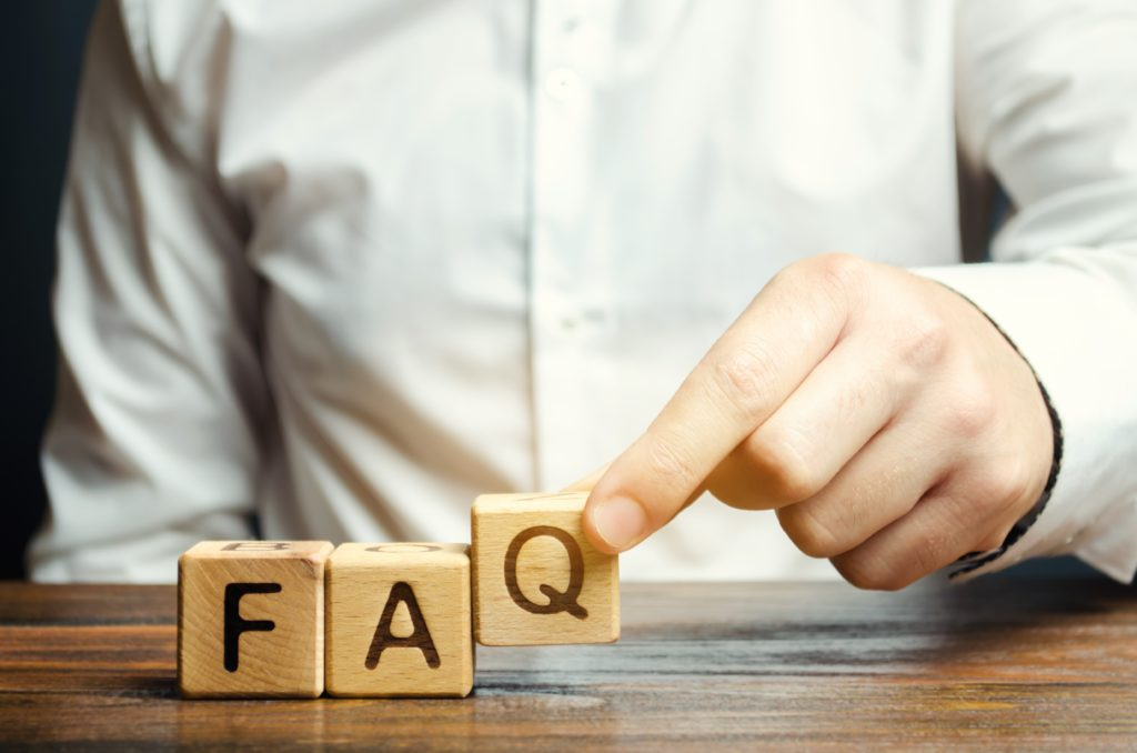 Close up of a man holding wooden blocks with letters positioned on a table and these make up the word FAQ
