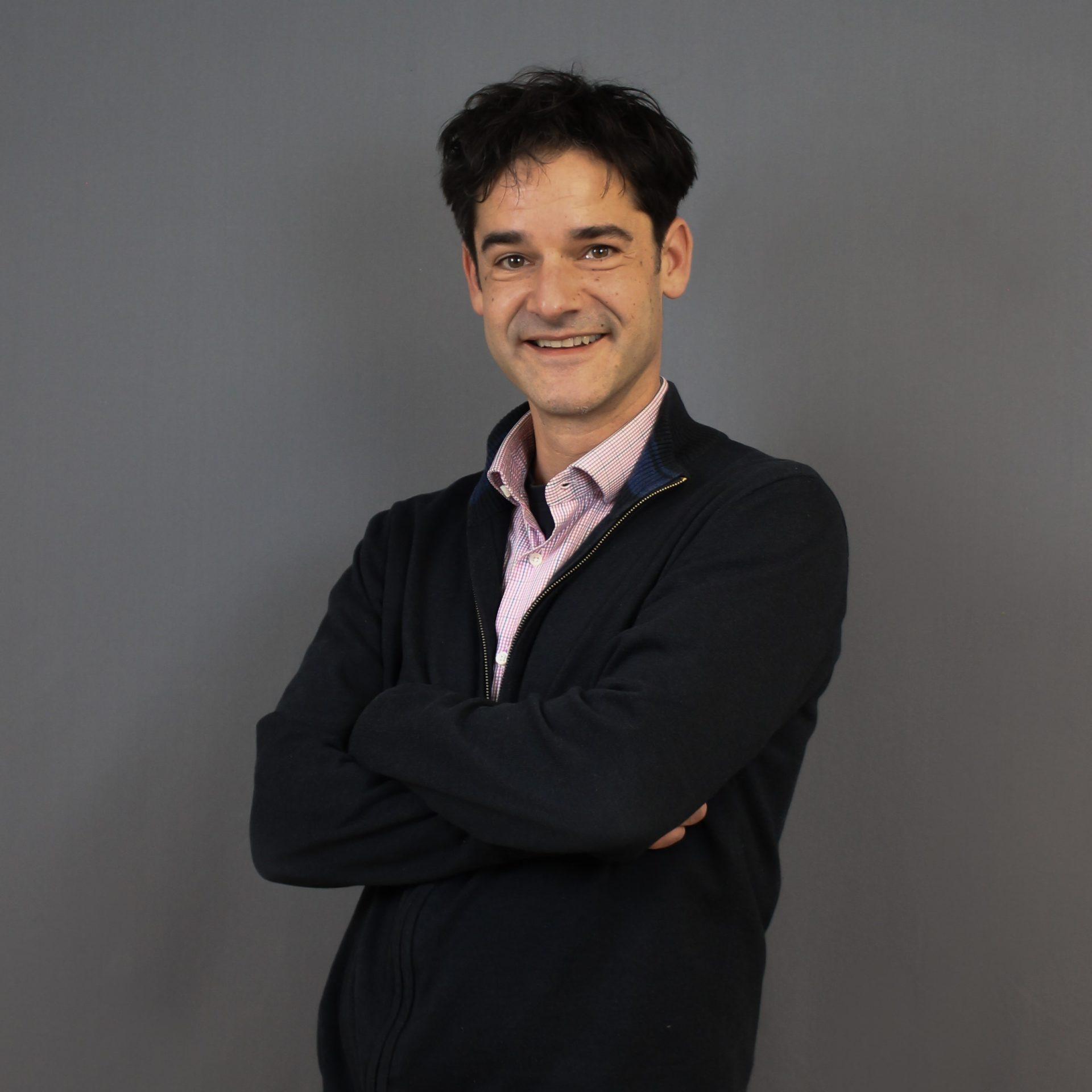 Ein Portrait von Karsten Wabnitz vor einem grauen Hintergrund mit quadratischen Maßen