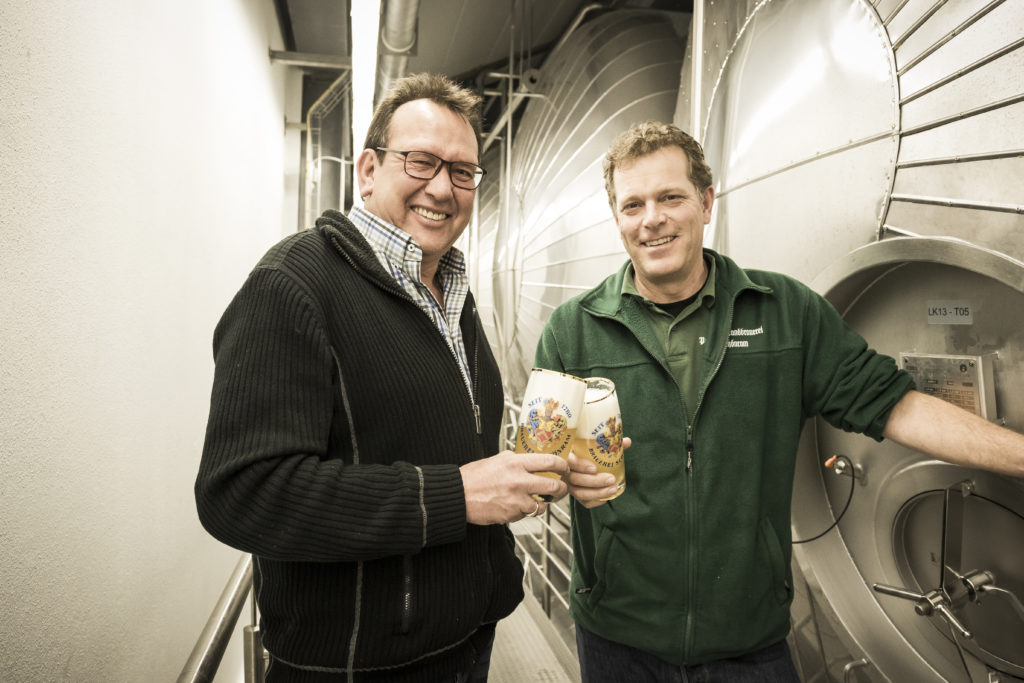 two men who toast a glass full of beer in a brewery