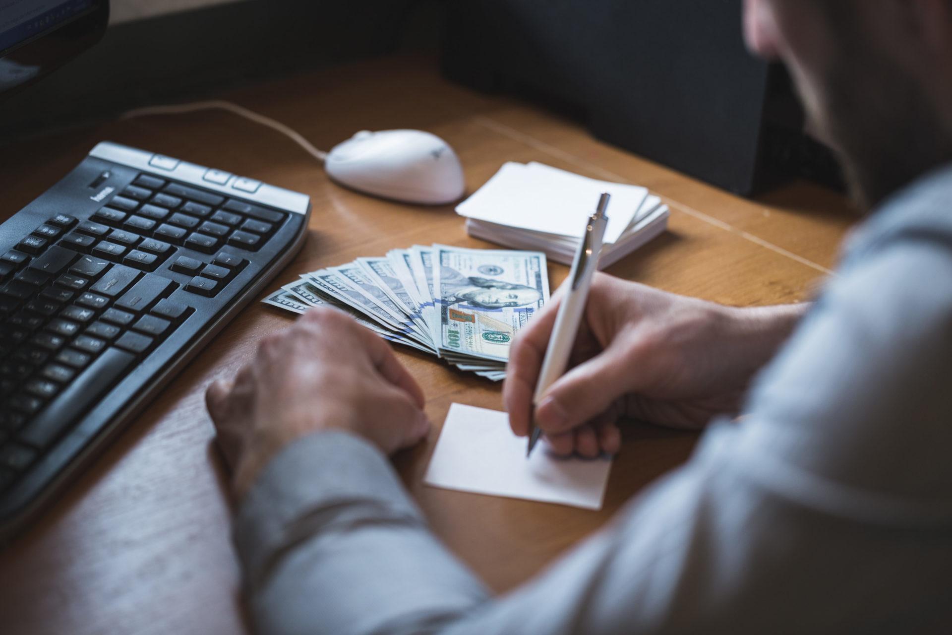 Ein Mann seitlich von hinten, der an einem Tisch mit einem Computer sitzt und Dollar Banknoten zählt