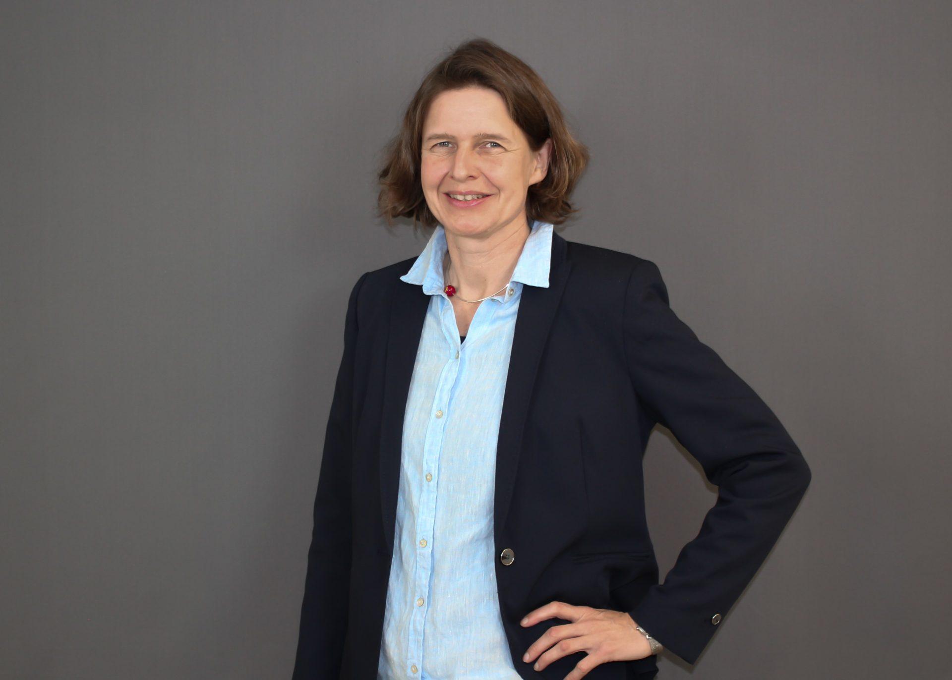 Ein Portrait von Kirsten Loewe vor einem grauen Hintergrund