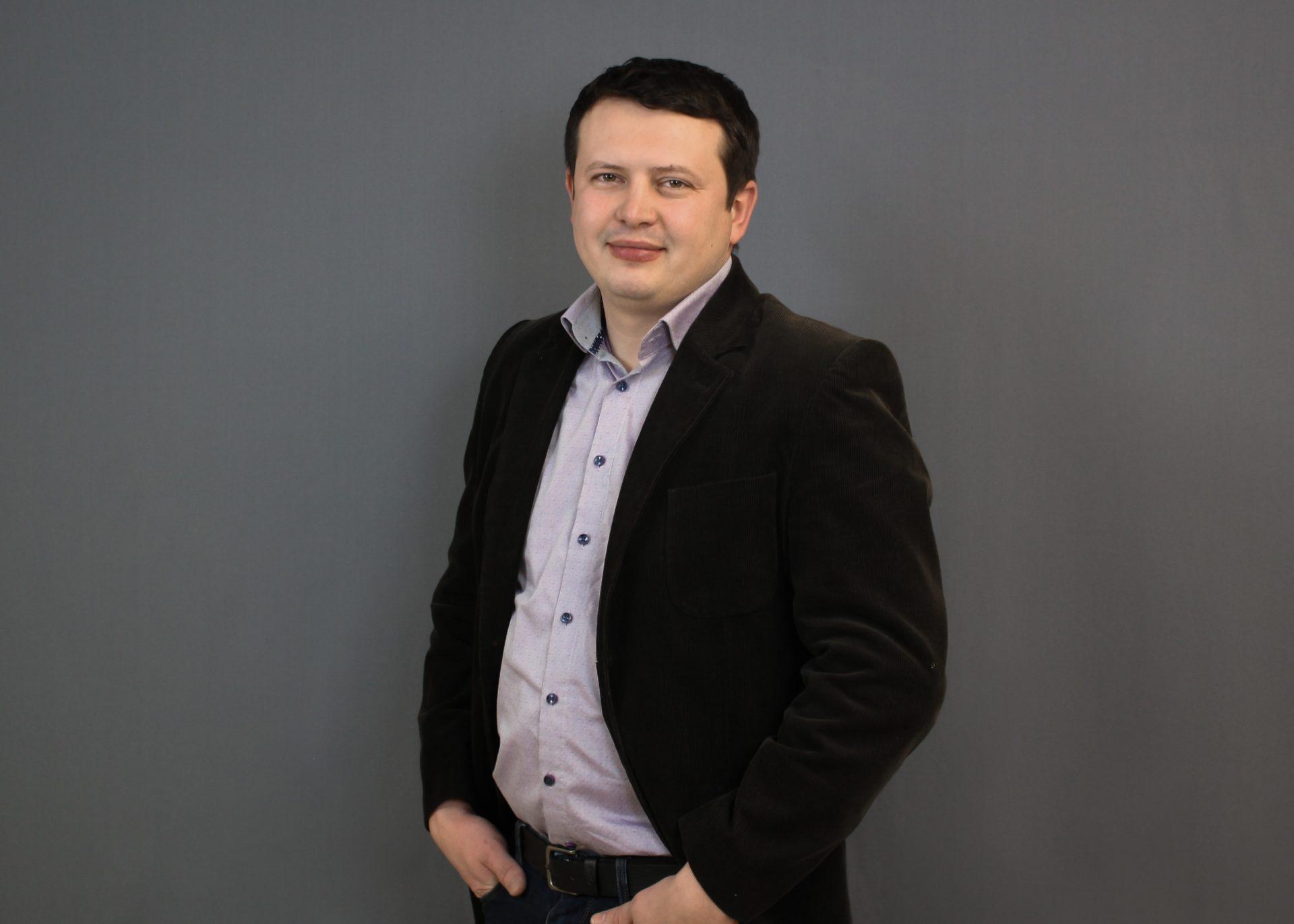 Ein Portrait von dem Chief Financial Officer Paul Bauer vor einem grauen Hintergrund