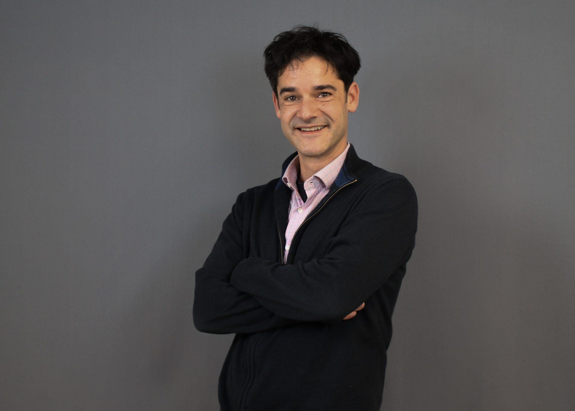 Ein Portrait von Karsten Wabnitz vor einem grauen Hintergrund