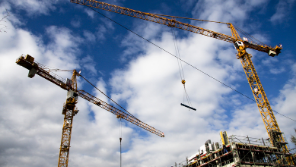 two construction worker cranes on a constraction site in the open air